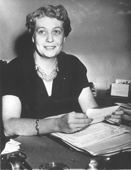 Photograph showing Grace Tully at work at her desk in the White House